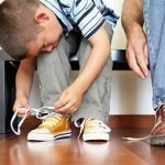 дете си връзва връзките на обувките